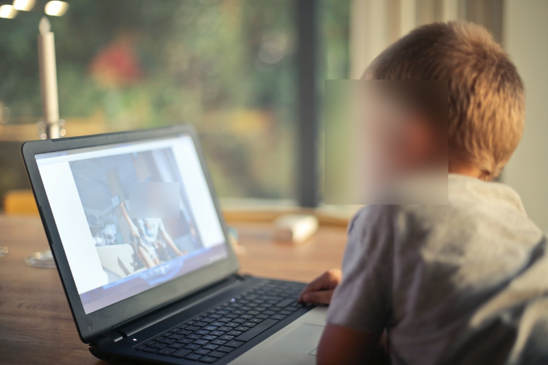 Boy Watching Video Using Laptop with faces blurred