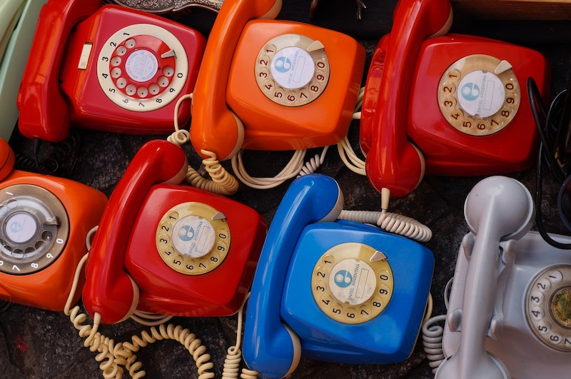 Seven rotary phones of different colours